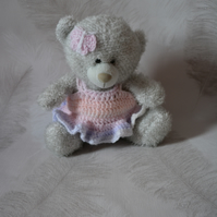 Small grey teddy bear in pastel coloured crochet dress and butterfly