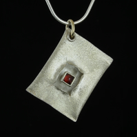 Hollow form pendant with garnet stone.