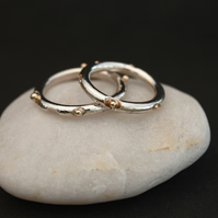 Silver ring with gold beads.