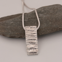 Cast silver abstract pendant on silver chain.