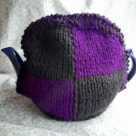 Purple and black knitted tea cosy.