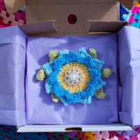 Blue hues crochet flower brooch with leaves and button centre.