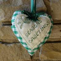 Christmas Decoration. Handmade heart with Seasons Greetings message.