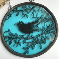 A small circular stained glass panel of a black bird