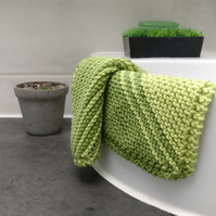 Two green knitted facecloths