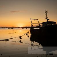 Boat Silhouetted at Sunrise