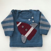 Hand knitted baby jumper with a rocket design