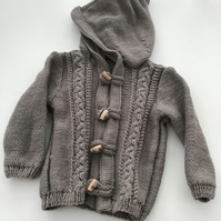 Hand knitted baby hooded jacket with toggle fastenings