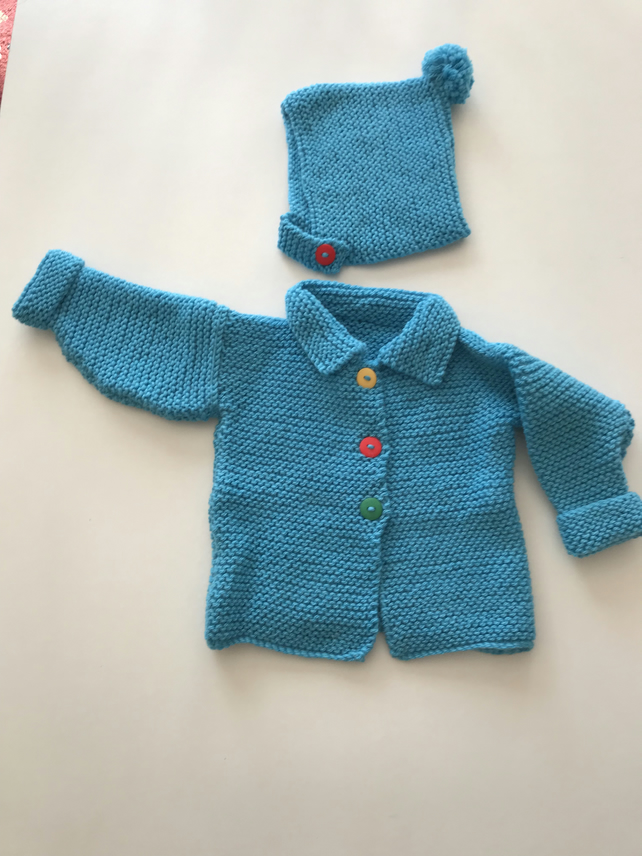 Chunky hand knitted baby jacket with a matching hat