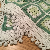 Beautiful handmade crocheted granny squares blanket with pretty pompom edge