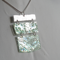 Three piece reflective pale green and silver pendant.