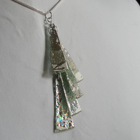Silver with white detail reflective pendant.