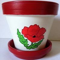 Terracotta plant pot in a Poppy design and matching red saucer.