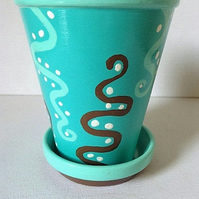 Tall flower pot and saucer in turquoise and brown abstract design.