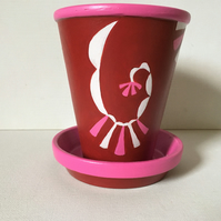 Tall terracotta plant pot and saucer.