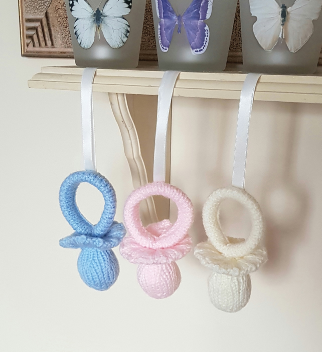 Hand-knitted hanging nursery decorations, pacifiers