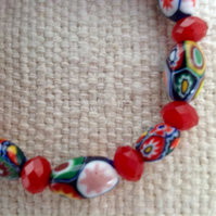 Millefiori bead bracelet with faceted red beads on strong stretch cord