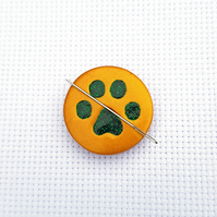 Cat paw needle minder. Gold with green glitter paw print.