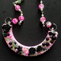 Black and pink flowers and rhinestones arch necklace on pink rosary chain
