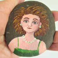 Stone painting of a girl in green dress.