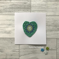 Card with crochet heart motif in greens, blue & grey, blank card