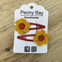Girls flower hair clips in orange, yellow & red