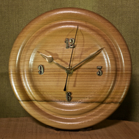Hand made circular elm wood wall clock with concentric rings design.