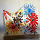 fused glass flower panel on an oak stand