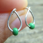 Silver drop shape stud earrings with tiny green seed bead