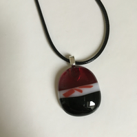 Black, red and white pendant made from fused glass