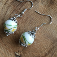 Yellow and green oriental design on a white painted ceramic bead earrings.