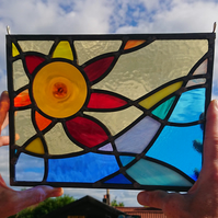 Stained glass amber-red sun and rolling wave, leaded hanging panel