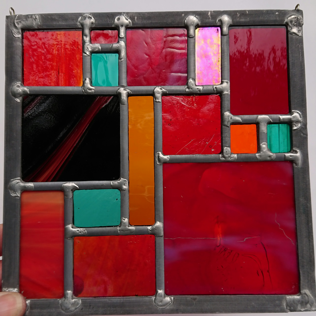 Stained glass geometric leaded panel - red, orange and jade.