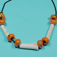 CLAY PIPE AND GLASS BEAD NECKLACE.