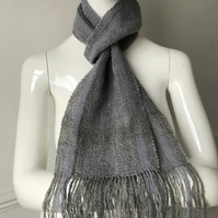 A hand dyed, hand spun, handwoven scarf in shades of grey and lilac.