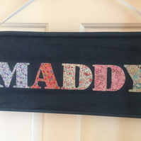 Personalised hanging name banner with hand-stitched lettering