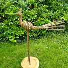 willow bird sculpture on a log round