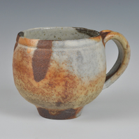 A wood-fired, stoneware cup with slip decoration