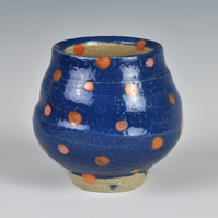A stoneware sake cup with pink and orange dots