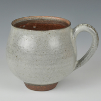 A wood fired stoneware tea or coffee cup with ash glaze