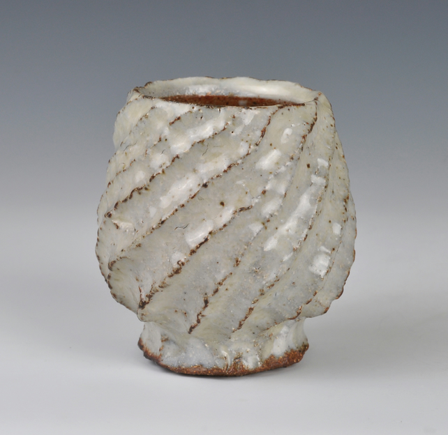 A carved, stoneware cup