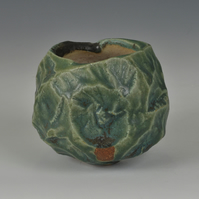 A carved, stoneware bowl with copper green glaze