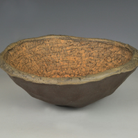 A carved earthenware bowl with terra sigillata