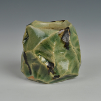 "A carved, stoneware ""guinomi"" or sake cup with Oribe glaze"
