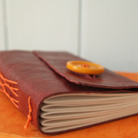 Red leather notebook with orange French stitch binding.