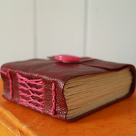 Red leather notebook with French stitch binding.