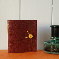 Tiny red leather notebook with pamphlet stitch binding.