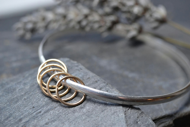 Sterling silver bangle with five gold rings