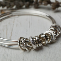 Three bangles with silver charms