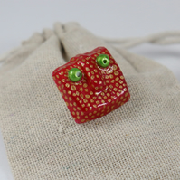red and gold monster face brooch